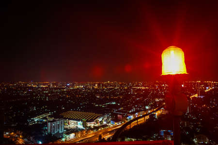 Indicator red light on the top of high tower with cityscape at night in background. Signal warning light for the aircraft. Safety zone