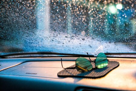Abstract emotional picture of raindrops and moisture on the car's front glass with blurred sunglasses in foreground Archivio Fotografico