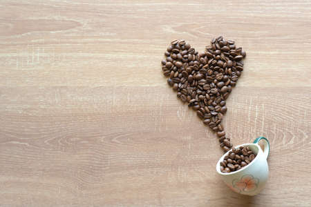 Many roasted coffee beans put of the ceramic cup into heart shape