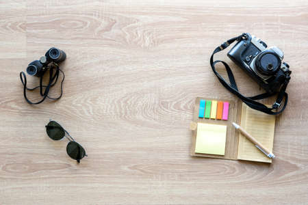Top view vintage camera, sunglasses, binoculars and notepad with pen on the wooden background with copy space for adding some text