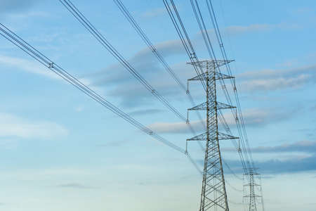 Low angle view of high voltage tower with electrical cable for distribution and blue sky background
