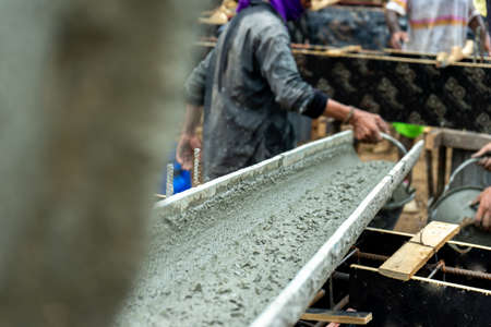Selective focus on the tray while delivering the mixed cement to the workers at the construction site