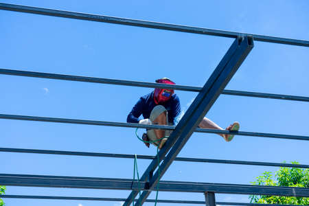 Worker welding the steel structure of roof with arc welding machine and blue sky in background