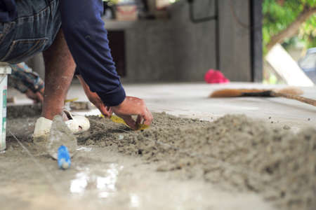 Selective focus on leg and hands of worker mearsuring the floor during installation the floor tiles in the ouse under construction Reklamní fotografie