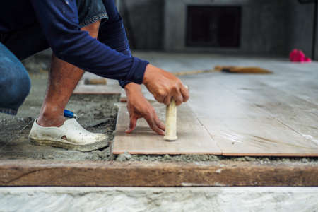 Selective focus on hand of worker installing the floor tile with motion blurred hand at the construction site