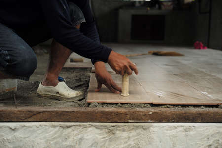 Motion blurred hand of worker installing the floor tile by wooden hammer at the construction site