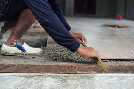 Selective focus on leg and hands of worker measuring the floor during installation the floor tiles in the ouse under construction Reklamní fotografie