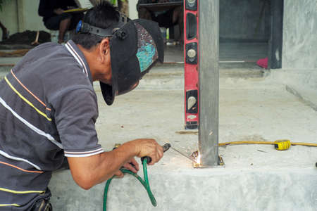 Welder with face shield is welding the steel column with the plate on the concrete floor at the construction site