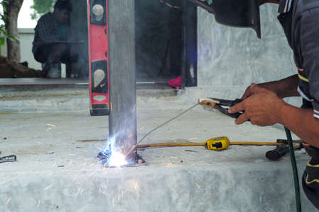 Welder with face shield is welding the steel column with the plate on the concrete floor at the construction site Stock fotó - 157979651