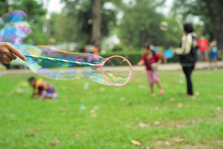 Hand holds the plastic ring for making bubble from soap with blurred group of people playing at the park in background