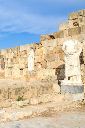 Vertical photography of ancient ruins and statues belonging to the famous Salamis complex in Northern Cyprus taken with blue sky above. The antique landmark is a popular tourist spot.