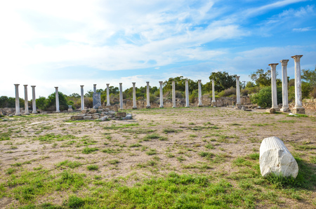 Group of marble Corinthian columns belonging to the complex of Salamis city ruins in Turkish Northern Cyprus. Taken on a beautiful day with light clouds above.