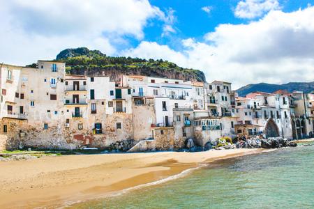 Case storiche tradizionali sulla costa del mar Tirreno in siciliano Cefalù, Italia. Dietro le case c'è la roccia che domina la città. La bellissima città italiana è una popolare attrazione turistica. Archivio Fotografico