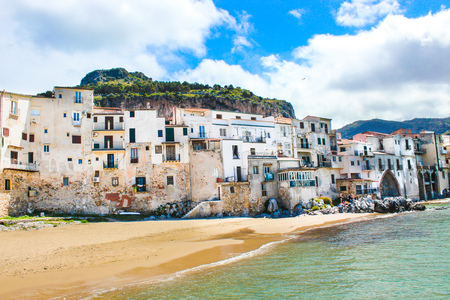 Traditional historical houses on the coast of Tyrrhenian sea in Sicilian Cefalu, Italy. Behind the houses there is rock overlooking the city. The beautiful Italian city is popular tourist attraction. Reklamní fotografie