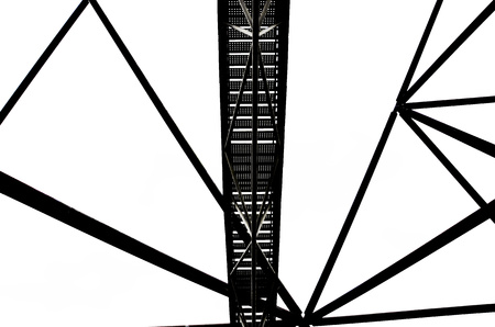 Incredible construction of the Tetrahedron in german Bottrop with stairs leading to the top of the view point captured on a black and white photography that was taken from below against the sky.