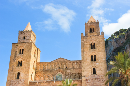 Cefalu Cathedral in Sicily, Italy with blue sky and rocks behind. Famous Roman Catholic basilica erected in Norman architectural style. 写真素材