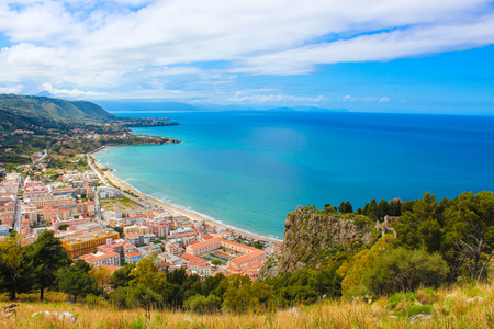 Stunning view over the bay on Tyrrhenian coast by city Cefalu, Sicily, Italy. On the adjacent rocks overlooking blue sea there are medieaval castle ruins Rocca di Cefalu. Popular tourist attraction.