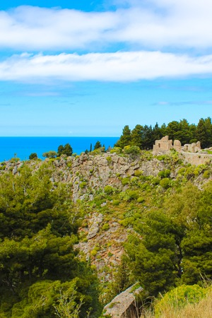 Medieval castle ruins Rocca di Cefalu captured on vertical photo with blue Tyrrhenian sea in background. The historical site is located over coastal city Cefalu in Italian Sicily.