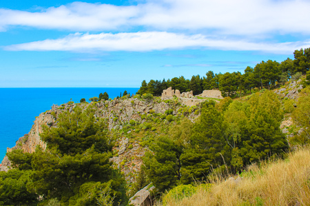 Ruins of Rocca di Cefalu on the rock overlooking the Tyrrhenian coast in Cefalu, Sicily, Italy. Medieval castle ruins are surrounded by green trees. The historical site is popular tourist attraction.