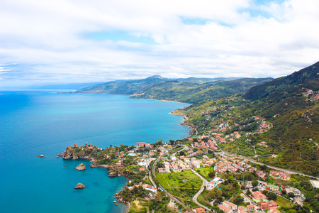 Beautiful view of picturesque Sicilian village on the Tyrrhenian coast from above captured from Rocca di Cefalu, Italy. Hilly landscape in background. Cefalu is a major tourist destination in Italy.