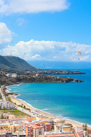Paraglider flying over the amazing sea landscape by coastal Cefalu in Italian Sicily. Captured on a vertical photography with hills behind the beautiful bay.