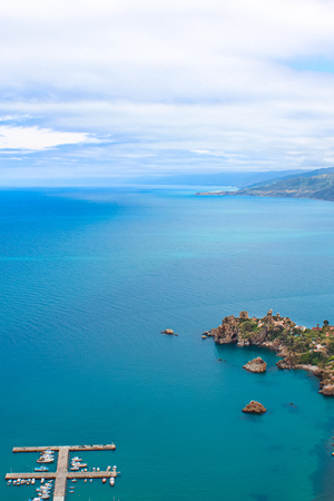 Dark blue calm water of Tyrrhenian sea surrounding the Sicilian coastal village Cefalu from above. Captured on vertical picture with pier and boats in the sea.