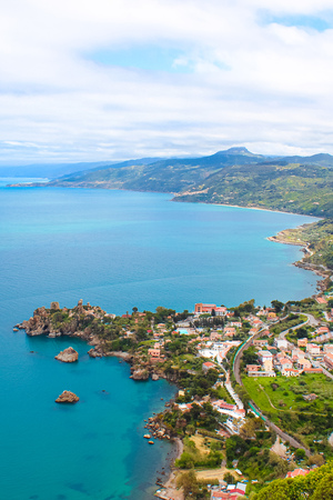 Amazing view of a bay surrounding the coastal Sicilian village Cefalu from above with the hilly landscape in the background. The beautiful city is a popular Italian holiday destination. Banco de Imagens