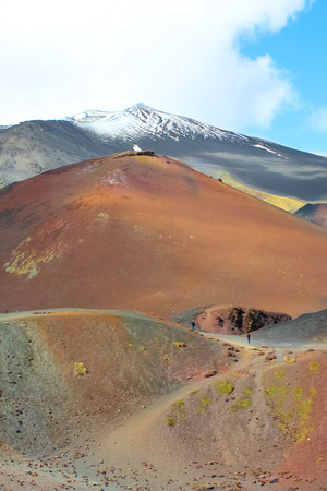 Etna volcano and adjacent Silvestri craters in Italian Sicily captured on a vertical photography. The damaged volcanic landscape is a popular tourist attraction. Snow on the very top of the mountain.
