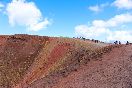 Tourists standing on the edge of Silvestri craters on Mount Etna in Italian Sicily. The colorful volcanic landscape is popular with hikers.