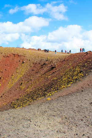 Tourists standing on the edge of Silvestri craters on Mount Etna in Italian Sicily. The amazing volcanic landscape is a popular tourist destination. Vertical photography.