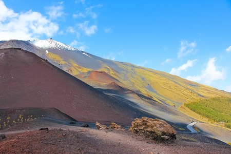Amazing volcanic landscape on Mount Etna, Sicily, Italy taken from adjacent Silvestri craters on a sunny day. Snow on the very top of the mountain. European highest active volcano.