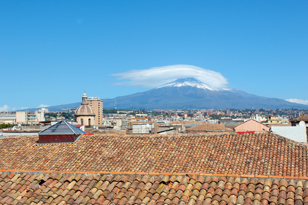 Cityscape of Sicilian Catania in Italy taken from the roof of a building in historical center. In the background there is famous Mount Etna volcano overlooking the beautiful city. Stock Photo