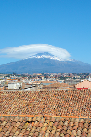 Vertical photography capturing beautiful cityscape of Catania, Sicily, Italy with famous Mount Etna volcano in background. Roofs of the historical buildings. Snow on the very top of the mountain.