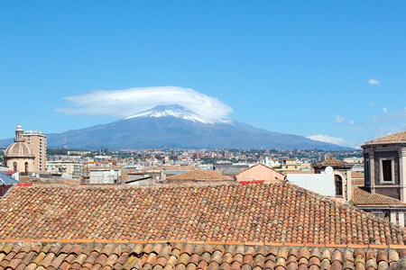Amazing cityscape of Sicilian Catania, Italy with roofs of historical buildings in the old town and majestic Etna volcano in the background. Snow on the very top of the mountain. Sunny day.