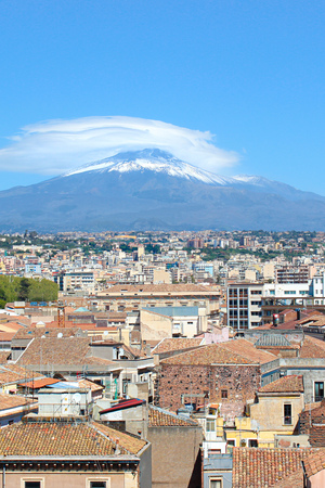 Vertical picture capturing famous Mount Etna overlooking the Sicilian city Catania, Italy. Smoke cloud over the famous volcano, snow on the top. The beautiful city is a popular tourist destination. Banco de Imagens