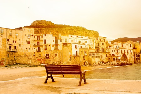 Empty bench on pier in Cefalu, Sicily, Italy in orange sunlight with historical buildings on the sea coast. Sunrise, sunset. Peace, peaceful and relax concept.