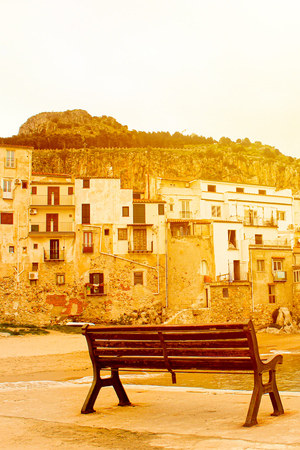 Empty bench captured on a vertical picture in bright orange sunset light. Taken on the coast of Sicilian city Cefalu, Italy. Historical buidlings and rocks in the background.