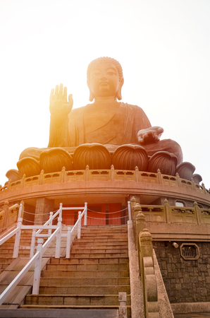 The enormous Tian Tan Buddha at Po Lin Monastery in Lantau Island, Hong Kong. Photographed during sunset with orange sun shining behind the statue. Popular tourist attraction.