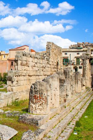 Vertical photography of ruins of the Temple of Apollo in Ortigia Island, Syracuse, Sicily, Italy. Colonnade ruins, famous archaeological site. Popular tourist attraction. Blue sky with clouds. Stok Fotoğraf