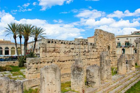 Significant ancient Greek ruins of the Temple of Apollo in Ortigia Island, Syracuse, Sicily, Italy. Colonnade remnants. Palm trees in background. Sunny day, blue sky. Popular tourist place.