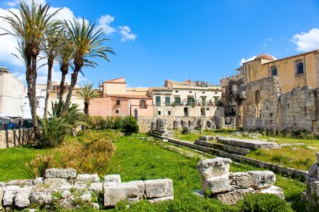 Amazing ruins of Temple of Apollo in Ortigia Island, Syracuse, Sicily, Italy. Significant ancient Greek monument, archaeological site. Temple ruins. Adjacent palm trees, sunny day, blue sky. Stok Fotoğraf
