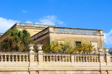 Lemon trees on historical balcony on Piazza Duomo Square in Syracuse, Sicily, Italy. The main square is located on famous Ortigia Island. Popular tourist attraction. Stock Photo
