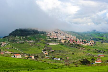 Amazing view of village Gangi in Sicily, Italy photographed in foggy weather. The historical city is located on the top of the hill. Green countryside landscape. Fog. Sicilian countryside. Stockfoto