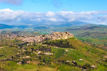 Beautiful view of Sicilian village Calascibetta taken with adjacent mountains and green landscape. The historical Arab city is located on the hill. Amazing tourist place in Italy.