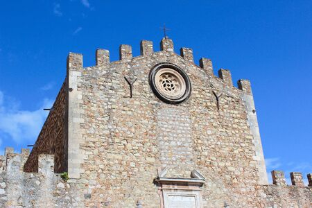 Detail of the facade of St. Nicholas Church, known also as Duomo di Taormina on a sunny day with blue sky. Sicilian city Taormina in Italy. Close up facade. Religious building.