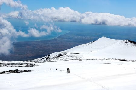 Amazing view from Mount Etna photographed with hikers going down on the snow and sea coast in the background. Magnificent clouds close to the top of the mountain. Etna, Sicily, Italy.