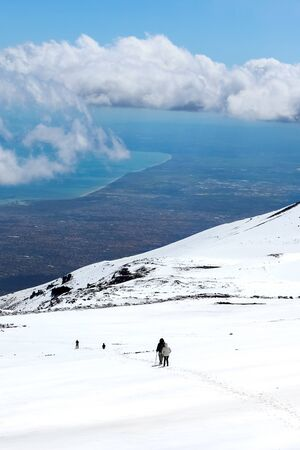 Stunning landscape taken from Mount Etna, Sicily, Italy. Hikers on the way down from the volcano. Snow on the mountain. Sicilian sea coast in the background. Popular travel destination. Banco de Imagens