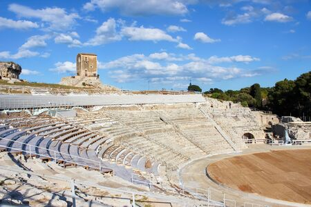 Ancient Greek Theatre of Syracuse in Sicily, Italy on a sunny day. Archaeological site, historical landmark. Popular tourist spot. Stage and tribunes ready for outdoor plays. Stok Fotoğraf
