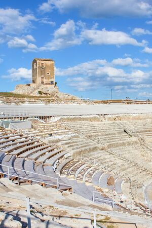 Famous Greek Theatre in Syracuse, Sicily, Italy with blue sky. Ancient site, historical landmarks. Popular tourist attraction. Stage and tribunes ready for outdoor plays, concerts and cultural events.