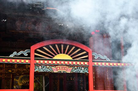 Taipei, Taiwan - May 13th 2017: Smoke cloud from incense sticks over red entrance in amazing Lungshan Temple in Taipei, Taiwan. Inner courtyard of religous complex. Religion symbol. Buddhism, taoism.